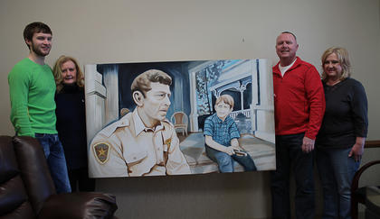 "Local artist Bettye Brookfield, a member of the Fine Arts Bardstown Society on Court Square in Bardstown, unveiled her latest painting Saturday at the Nelson County Sheriff's Office. Brookfield's 36 x 60 painting, called ""A Sheriff's Wisdom and Protection,"" depicts beloved TV Sheriff Andy Taylor and his son Opie sitting on the porch of their home. Opie has a black eye, having recently gotten into a fight at school, and Andy is sitting down with him to talk about it. Brookfield said the painting reflects the idea that, sometimes first responders are family members and that officers must balance the demands of their job with the demands of their home. ""They are men and women with families and people who love them,"" she said of police officers. ""Their work requires them to leave those comforts to serve and protect our communities."" Brookfield said she chose the subject because she wanted to paint something soothing and uplifting, ""returning to an innocent era like Mayberry."" ""Our officers are ordinary people who sometimes are called upon to perform extraordinary duties,"" she said."