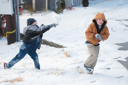 Mathias Jenkins, 6, pelts his brother, Zander Jenkins, 8, with a snowball after a January storm dropped a blanket of snow on Nelson County.