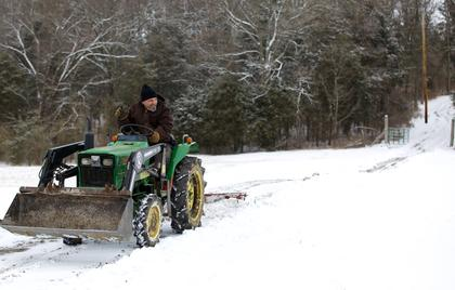 Danny Tarter uses a tractor and plow to clear his 1,000-foot driveway in Cox's Creek Monday.