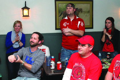 Red-blue sibling rivalry: brothers Michael St. Peter (in the UK T-shirt) and Mark St. Peter (standing in front of the picture) were pulling for opposing teams during the Kentucky-Louisville NCAA matchup Friday night at the Hilltop Inn.