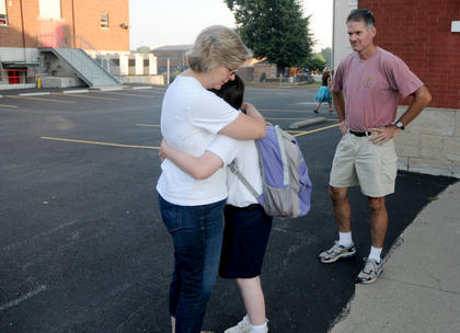 "Mary Mattingly hugs her daughter Laura, on her first day of fifth grade at St. Joseph School Aug. 2. Mary's father Scott stands nearby. ""This is our routine,"" Mary Mattingly said. ""We have not grown out of hugging on the first day of school."""