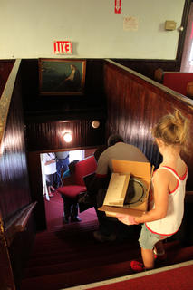 Reagan Trzop, 5, helps carry items down the stairs from the sanctuary and out of the 199-year-old First Baptist Church, which will be renovated to create a Reverend Roy Henry Educational Center.
