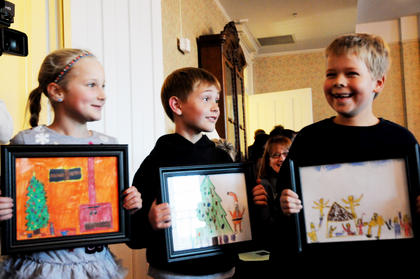 Saint Joseph School second-graders Madeline Meredith, Seth Medley and Davis Boone, hold artwork they designed for a postage stamp contest at Nazareth Friday.