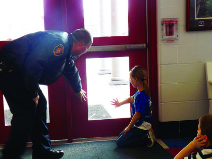 A Bloomfield firefighter asks second-grader Trinity Smith to demonstrate how to feel for heat on a door in a possible fire as part of Bloomfield Elementary's STEAM Day.