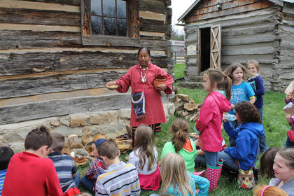 Tina Hagee teaches children from Cox's Creek Elementary School about Native American ways while showing them artifacts. Hagee portrays a North American Indian but is Jamaican.