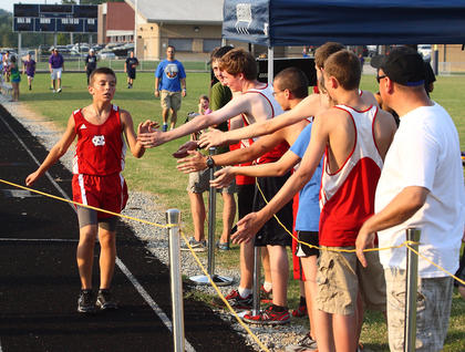 Steven Perry (left), an eighth-grader at OKH, is greeted by the Nelson County varsity runners after winning the Thomas Nelson Weeknight Warfare middle school race Tuesday.