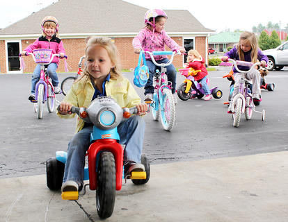 Four-year-old Natilie Carey leads the pack at Little Angels Primary House's annual Trike-a-thon, a fundraiser for St. Jude Children's Hospital. Participating students collect donations from family and friends and then get to ride their bikes and trikes for an hour of the school day.