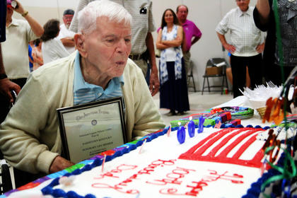"Rush ""Tuffy"" Weeks, clutching his certificate from being announced as an honorary American Legion Post 42 member, blows out his candles during a surprise 100th birthday party at Bardstown United Methodist Church."