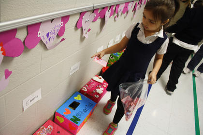 Kindergartner Lauren Whelan walks to find the right box to put in a card for Valentine's Day at Bardstown Primary Friday.