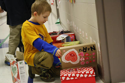 Kindergartner Xavior Green places a card in a classmate's box for Valentine's Day at Bardstown Primary Friday.