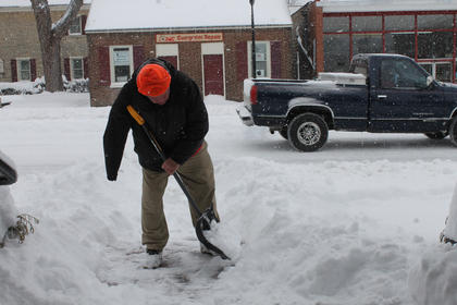 Walter Lee Frasier clears the snow from the sidewalk in front of Mammy's Kitchen Thursday morning.