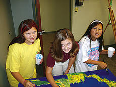 """<div class=""""source"""">Photo Submitted</div><div class=""""image-desc"""">Left to right- Smocked out to avoid splashes, Madeline Metcalf, Anna Vincent, and Lauren Carrico add painted detail to their maps.</div><div class=""""buy-pic""""></div>"""