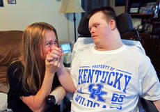"""<div class=""""source"""">KACIE GOODE/The Kentucky Standard</div><div class=""""image-desc"""">Kay Rogers kisses her son Jarett's hand as they sit inside their Bardstown home. The fact that Jarett, who has lost his independence following brain damage from chemotherapy, can still smile is what gets her through the day and gives her hope.</div><div class=""""buy-pic""""><a href=""""/photo_select/90192"""">Buy this photo</a></div>"""