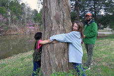 """<div class=""""source"""">KACIE GOODE/The Kentucky Standard</div><div class=""""image-desc"""">PeggyAnn Lynch and Clara Keaney were excited to cross an item off their Bernheim seek and find list — a tree so big they could wrap their arms around it. The walk around Two Ponds Loop, lead by Dan Pascucci, was one of the kid-friendly activities for the forest's first day of spring break week.</div><div class=""""buy-pic""""><a href=""""/photo_select/84605"""">Buy this photo</a></div>"""