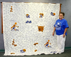 """<div class=""""source"""">Peter W. Zubaty</div><div class=""""image-desc"""">Bardstown's Darleene Wimsett shows off the fruit of 18 years of dedication in her 9x9-foot quilt featuring the hand-stitched names of every University of Kentucky coach and player since 1903. Last week, during Kentucky's win in the NCAA Championship game over Kansas, the quilt went up for auction on the Internet site eBay. </div><div class=""""buy-pic""""><a href=""""/photo_select/36580"""">Buy this photo</a></div>"""