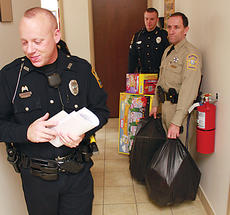 "<div class=""source"">FRANK JOHNSON/The Kentucky Standard</div><div class=""image-desc"">Bardstown Police Department officer Jason Woodson, left, smiles as he passes by officer Mike Medley, right, and Nelson County Sheriff's Deputy Steve Campbell, far right, who are loaded down with presents. Woodson has been with the Bardstown Police Department for five years and has helped organized Christmas for Kids each year. </div><div class=""buy-pic""><a href=""/photo_select/22254"">Buy this photo</a></div>"