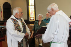 "<div class=""source"">RANDY PATRICK/The Kentucky Standard</div><div class=""image-desc"">Father Karl Lusk, priest at the Episcopal Church of the Ascension, reads from the Gospels during a Eucharistic service while Dave Bryant holds the Bible. At right are Ray and Shirley Patterson, parishioners at Ascension.</div><div class=""buy-pic""><a href=""/photo_select/77610"">Buy this photo</a></div>"