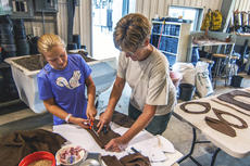 "<div class=""source"">KACIE GOODE/The Kentucky Standard</div><div class=""image-desc"">Bernheim volunteer Sandy Nafziger helps 10-year-old Elinor Troutt cut out fabric for a wearable nature creation Sunday during a workshop by British artist Ashley Peevor.</div><div class=""buy-pic""><a href=""/photo_select/97165"">Buy this photo</a></div>"