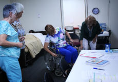 """<div class=""""source"""">KACIE GOODE/The Kentucky Standard</div><div class=""""image-desc"""">Sue Fawkes and Sue Bennett, Bardstown at Home Board members, demonstrate wheelchair transport approaches during a caregiver training session last week. </div><div class=""""buy-pic""""><a href=""""/photo_select/78299"""">Buy this photo</a></div>"""
