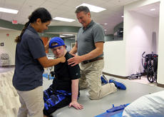 """<div class=""""source"""">KACIE GOODE/The Kentucky Standard</div><div class=""""image-desc"""">Occupational therapist Scott Burgener and physical therapist Melina Upton work with 20-year-old Jarett Rogers to build his balance. Jarett suffered neurotoxicity three years ago from chemotherapy treatments he was receiving for leukemia. The damage took away his ability to speak, eat on his own and function independently.</div><div class=""""buy-pic""""><a href=""""/photo_select/90198"""">Buy this photo</a></div>"""