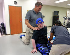 """<div class=""""source"""">KACIE GOODE/The Kentucky Standard</div><div class=""""image-desc"""">Occupational therapist Scott Burgener and physical therapist Melina Upton work with 20-year-old Jarett Rogers to build his balance. Jarett suffered neurotoxicity three years ago from chemotherapy treatments he was receiving for leukemia. The damage took away his ability to speak, eat on his own and function independently.</div><div class=""""buy-pic""""><a href=""""/photo_select/90199"""">Buy this photo</a></div>"""