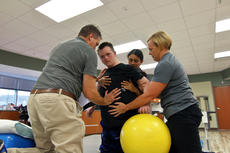 """<div class=""""source"""">KACIE GOODE/The Kentucky Standard</div><div class=""""image-desc"""">Occupational therapist Scott Burgener, physical therapist Melina Upton and therapy assistant Kim Ray work with 20-year-old Jarett Rogers to build his balance. Jarett suffered neurotoxicity three years ago from chemotherapy treatments he was receiving for leukemia. The damage took away his ability to speak, eat on his own and function independently.</div><div class=""""buy-pic""""><a href=""""/photo_select/90200"""">Buy this photo</a></div>"""