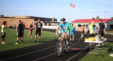 """<div class=""""source"""">KACIE GOODE/The Kentucky Standard</div><div class=""""image-desc"""">Track coach Dan Bradley rides through the crowd Monday after leading the 10K participants through the course.</div><div class=""""buy-pic""""><a href=""""/photo_select/79274"""">Buy this photo</a></div>"""