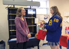 """<div class=""""source"""">KACIE GOODE/The Kentucky Standard</div><div class=""""image-desc"""">Clerk Jennifer Cissell presents Lexi Morris with a special gift, thanking the Bethlehem student for designing this year's cancellation stamp for the Nazareth post office.</div><div class=""""buy-pic""""><a href=""""/photo_select/82074"""">Buy this photo</a></div>"""