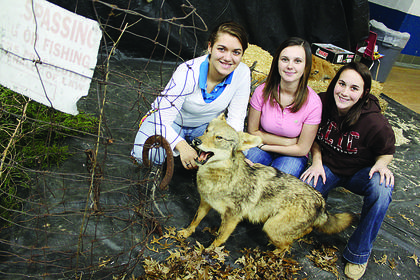 Students in Junior Dugan's outdoor living class pose in the wildlife display they set up in the Nelson County High School gym Dec. 15. Pictured are, from left, senior Megan Clark, junior Andrea Barnes and junior Heather Hoffman.