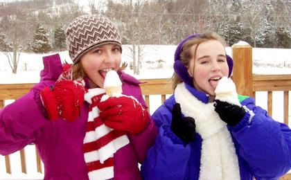 """Grace Frederick and Elizabeth Spalding enjoy authentic """"snow cones"""" while spending time outdoors during a recent snow day in Nelson County. Submit your """"Fun in the Snow"""" pictures online."""