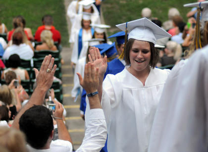 Hannah Spalding gives a high five as she walks up the aisle after graduating at The J. Dan Talbott Ampitheatre Sunday.