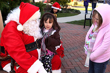 At first she was hesitant, but at her sister's urging, Olivia Sanders, 3, finally sat on Santa's lap in front of the Old Courthouse Saturday. Older sister Macaden Sanders, 7, looks on.