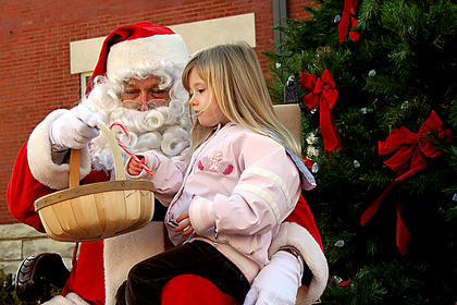 Autumn Johnson, 4, Bardstown, gets a candy cane from Santa Claus in front of the new Christmas tree in front of the Old Courthouse on Court Square shortly after noon Saturday. Santa will return Dec. 17 to offer more kids an opportunity to visit.