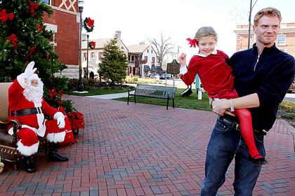 Ruby O'Bryan, 5, gets a candy cane after visiting Santa in front of the Old Courthouse in Bardstown on Saturday. Dad Kelly O'Bryan, Bardstown, holds Ruby. Santa on the Square will return for one more weekend, 11 a.m.-1 p.m. Dec. 17.