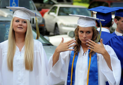 Bethlehem graduate Allison Patrick (left) stands next to Kate Spaulding as she fans herself to stay cool Sunday.