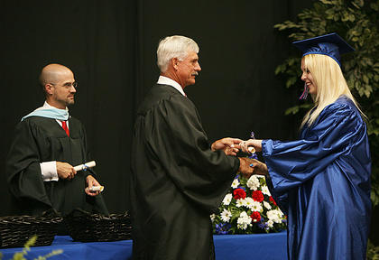 Nelson County School Board Chair Adam Wheatley shakes the hand of a 2011 Nelson County High School graduate June 3. Superintendent Anthony Orr is at left.