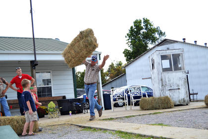 P.J. Milburn tosses a hay bail in a competition to see who could throw it the farthest at Young Farmers Day Saturday.