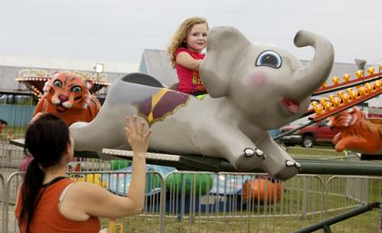 Hope O'Bryan, 3, rides a carnival merry-go-round while her mom, Bridget, waves Monday night at the Nelson County Fair.