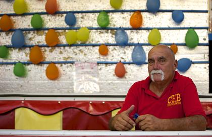 """Alan Mancise mans a booth at the Nelson County Fair Monday night. The Louisiana native, who said he also goes by Hulk Hogan and describes himself as """"a pure ragin' Cajun,"""" has worked the fair circuit for six years. Previously, he was an offshore cook in Louisiana, but wound up working the carnival due to a joke with a best friend. Mancise said he loves the job. """"I've seen the world,"""" he said. He travels seven months out of the year, usually starting the circuit in February or March."""