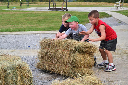 Lane Prather, Landon Miller and Tate Milburn play with a hay bail at Young Farmers Day Saturday.