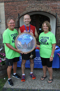 Leon and Margaret Claywell of Medica Pharmacy and Wellness Center, presenting sponsors of the Nelson County Community Clinic's Run for the Health of It 5K Saturday, bestow the first-place prize barrelhead to the overall winner of the men's competition, Troy Kolb of Louisville, principal of Bernheim Middle School. He won with a time of 19:28.
