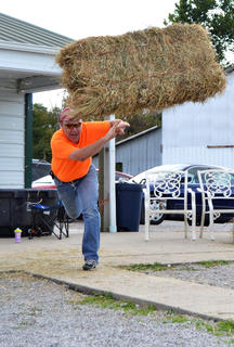 Timothy Prather tosses a bale of hay