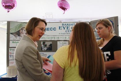 Dr. Lisa Woody, left, speaks with Megan Mattingly and Courtney Mattingly about the importance of eye exams for toddlers. Dr. Woody set up a booth at the Flaget Baby Fair.