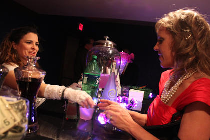 """Bartender Chenoa Veluzat, Bardstown, hands over the specialty cocktail, """"Purple Rain,"""" to Robyn Crume, Bardstown."""