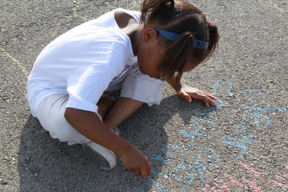 Kindergartner Janeil Blunt welcomes the morning with a sidewalk-chalk message at Bardstown Primary School's Tigerpawlooza field day June 2, 2011.