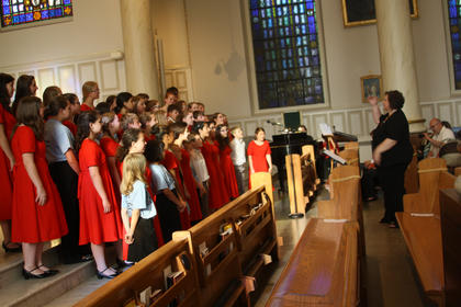 Lori Bammesberger, conductor of the Colorado Springs Children's Choir, leads her choir, along with some local singers from the Skip-To-Mi Farm Music Camp during a performance at St. Joseph Proto-Catherdral Saturday.