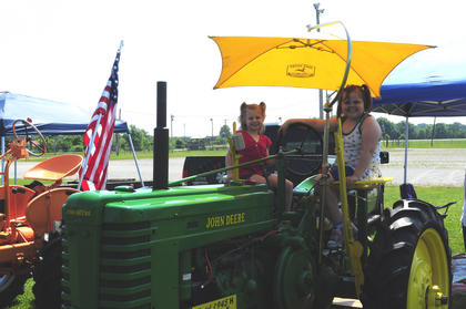 Tabetha and Keira Durbin, Bardstown, stay cool under the shade while sitting atop a 1944 John Deere tractor.