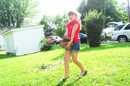 Reagan Trzop, 6, carries bricks away from the house so the house can be power washed.