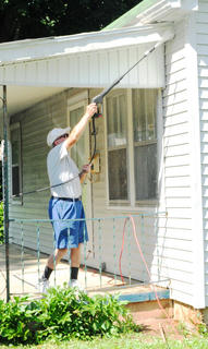 Millard Boggs, member of American Legion Old Kentucky Home Post 121, power washes the front of the home.