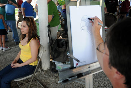 Clara Gomez sits as Denny Whalen draws a caricature at The Salt River Picnic.